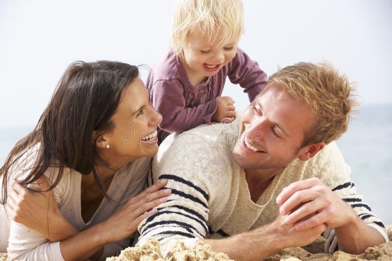Familia que se sienta en la playa junto imagen de archivo