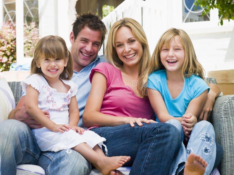 Familia que se sienta en la sonrisa del patio imágenes de archivo libres de regalías