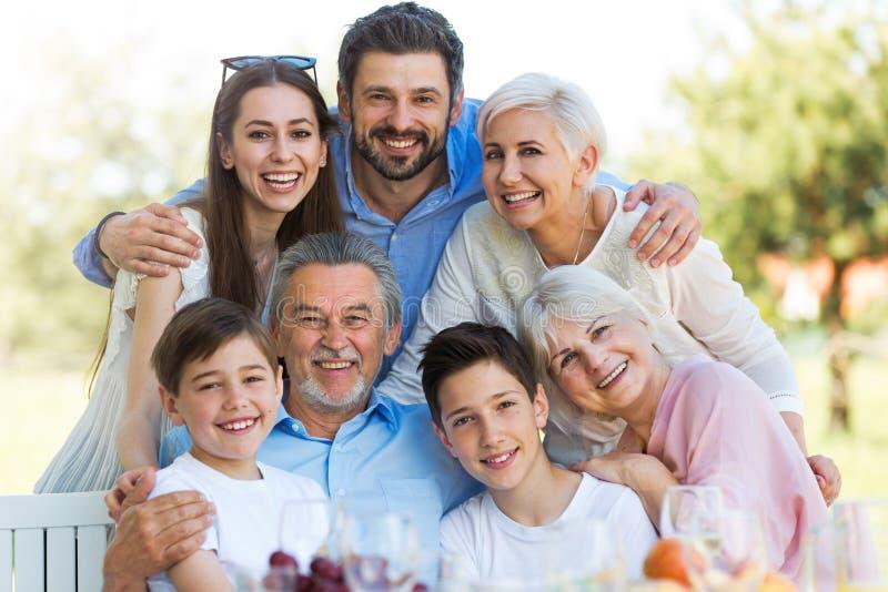 Familia que se sienta en la tabla al aire libre, sonriendo foto de archivo libre de regalías
