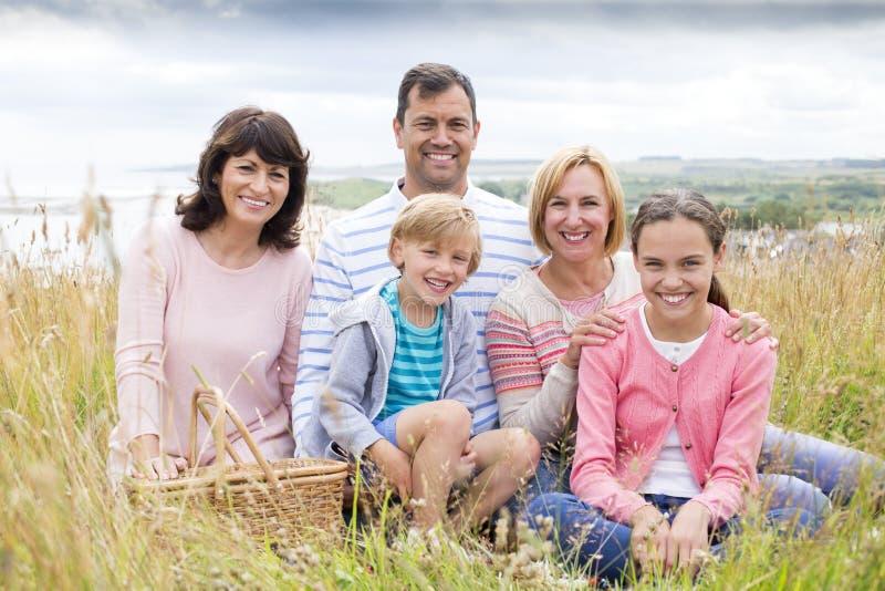 Familia que se sienta en las dunas de arena imágenes de archivo libres de regalías
