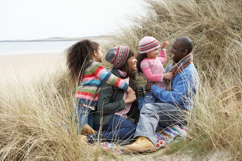 Familia que se sienta en las dunas que disfrutan de comida campestre el invierno imagen de archivo libre de regalías