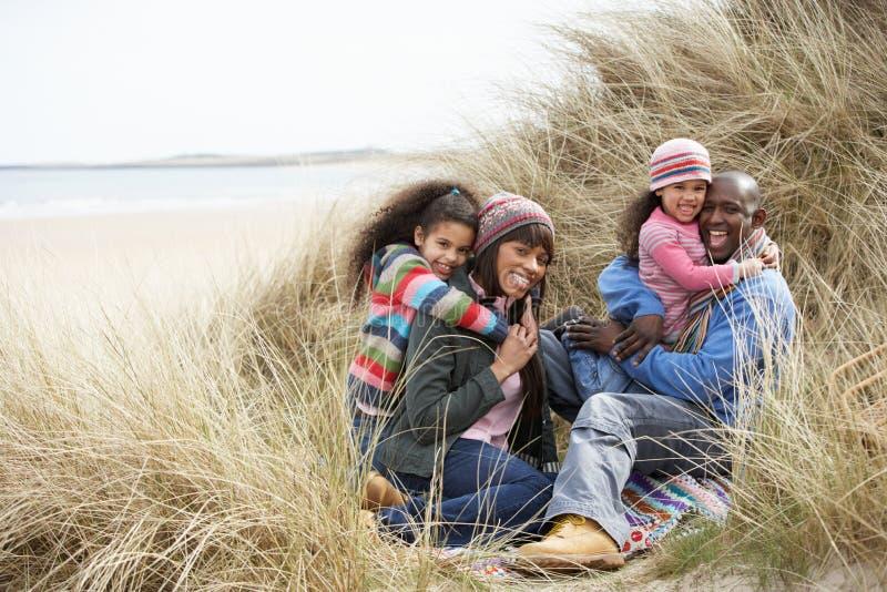 Familia que se sienta en las dunas que disfrutan de comida campestre el invierno imágenes de archivo libres de regalías