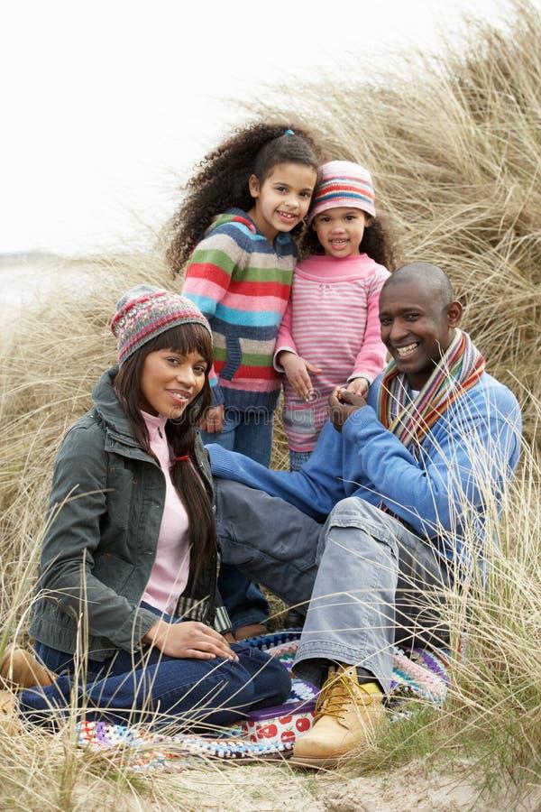 Familia que se sienta en las dunas que disfrutan de comida campestre el invierno imagen de archivo