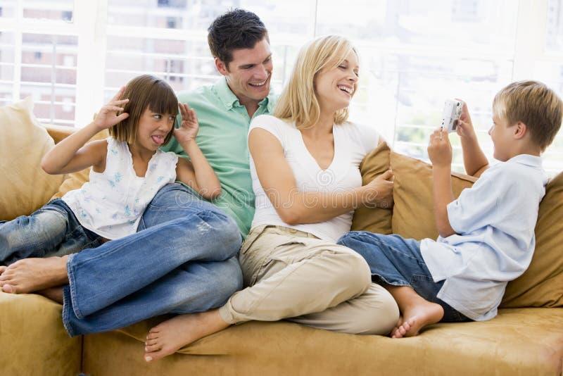 Familia que se sienta en sala de estar con las cámaras digitales fotos de archivo libres de regalías