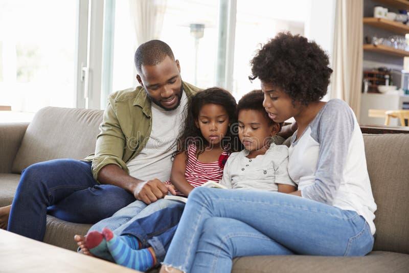 Familia que se sienta en Sofa In Lounge Reading Book junto imágenes de archivo libres de regalías
