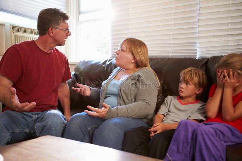 Familia que se sienta en Sofa With Parents Arguing foto de archivo