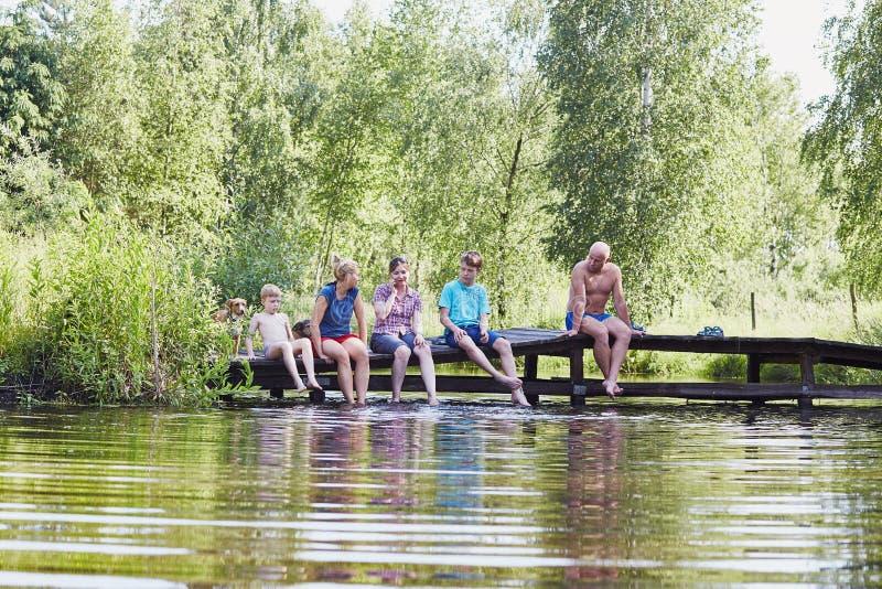 Familia que se sienta en un puente sobre un lago durante vacaciones de verano fotografía de archivo