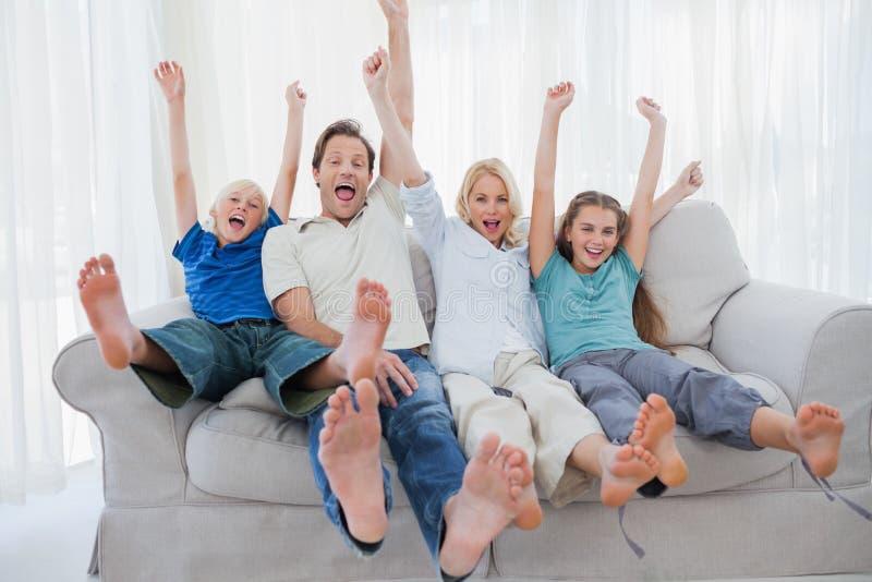 Familia que se sienta en un sofá y que aumenta los brazos foto de archivo