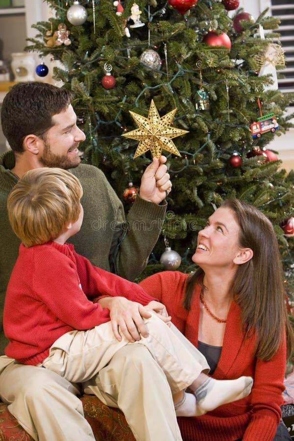 Familia que se sienta por el árbol de navidad, estrella de la explotación agrícola del papá fotos de archivo libres de regalías