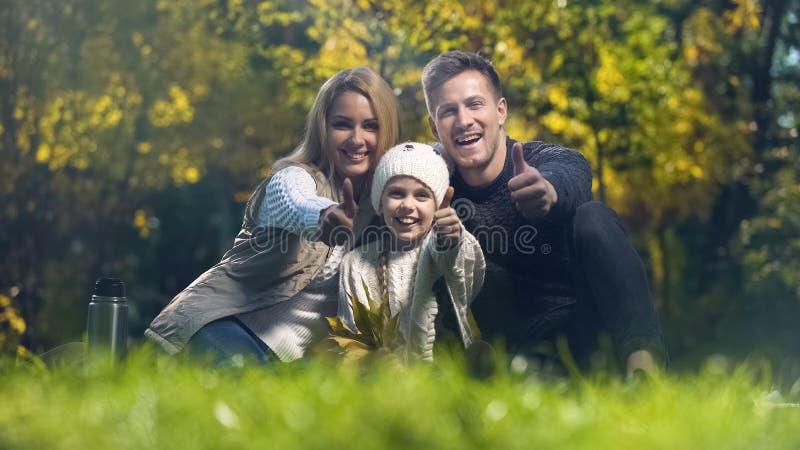 Familia que sonríe y que muestra los pulgares para arriba en la comida campestre en parque del otoño, paternidad imagen de archivo libre de regalías