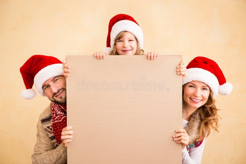 Familia que sostiene el cartel de la Navidad fotos de archivo