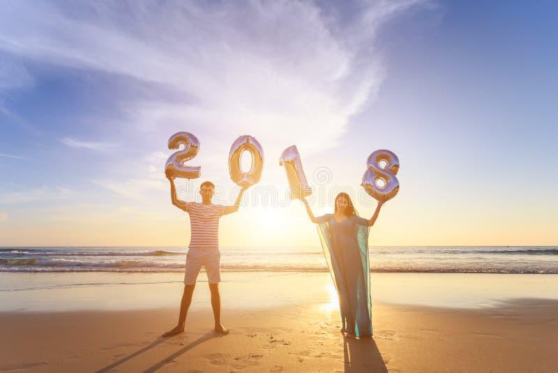 Familia que sostiene el globo 2018 del número en la playa en el ti de la puesta del sol fotos de archivo