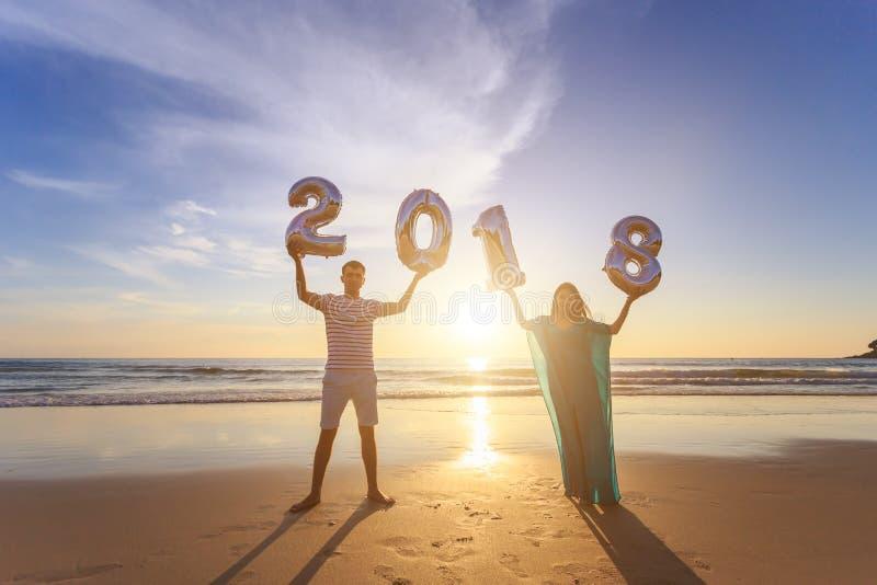 Familia que sostiene el globo 2018 del número en la playa en el ti de la puesta del sol imagen de archivo