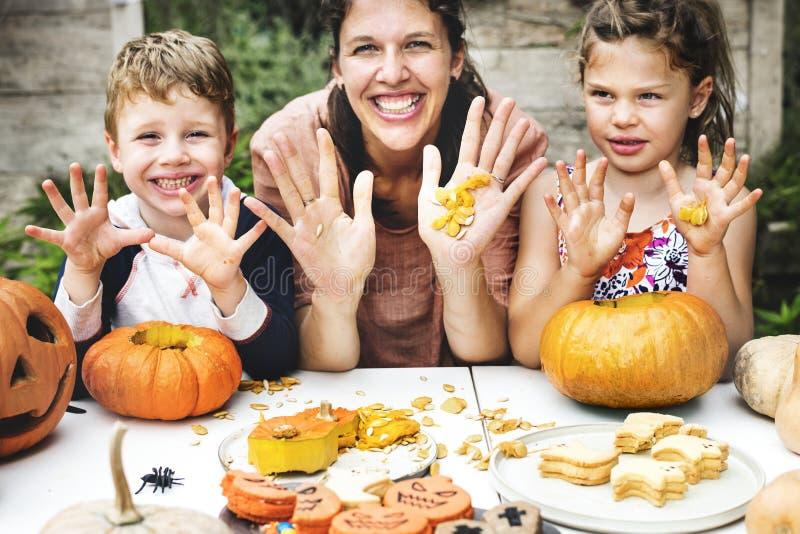 Familia que talla el ` de Halloween Jack-o - linternas imagen de archivo