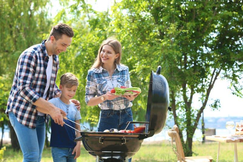 Familia que tiene barbacoa con la parrilla moderna al aire libre fotografía de archivo libre de regalías