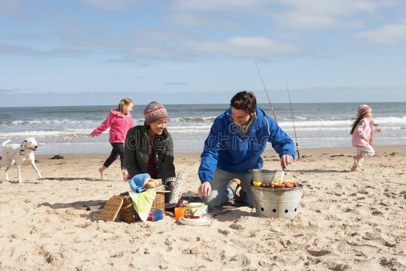Familia que tiene barbacoa en la playa del invierno imágenes de archivo libres de regalías