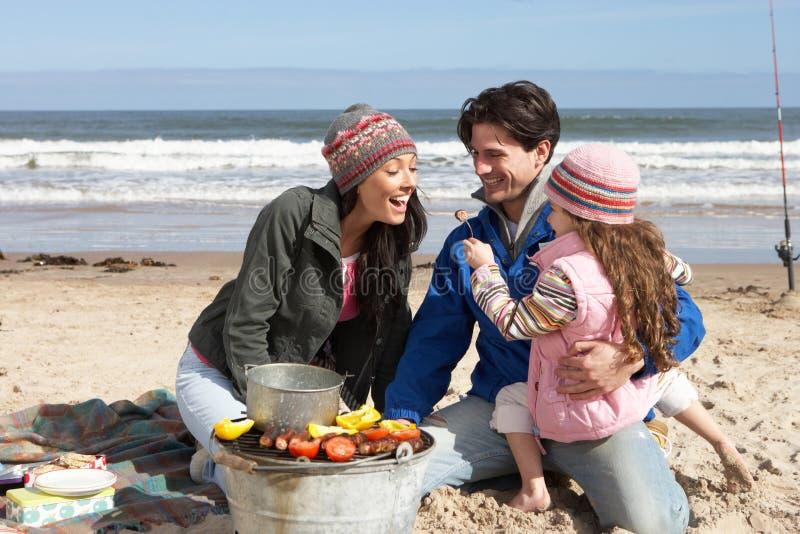Familia que tiene barbacoa en la playa del invierno fotos de archivo