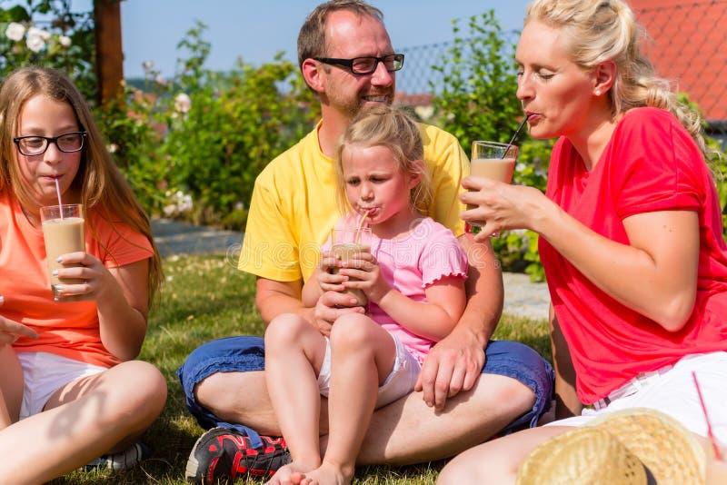 Familia que tiene comida campestre en frente del jardín de su hogar imagen de archivo