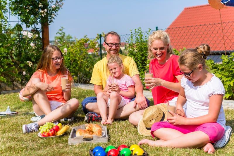 Familia que tiene comida campestre en frente del jardín de su hogar fotografía de archivo