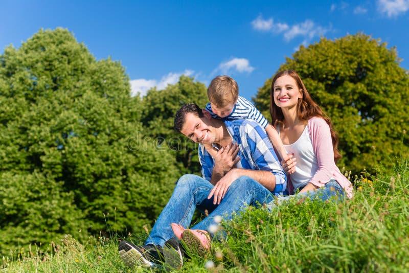 Familia que tiene comida campestre que se sienta en hierba en prado imagenes de archivo