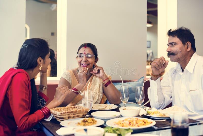 Familia que tiene comida india junto fotografía de archivo