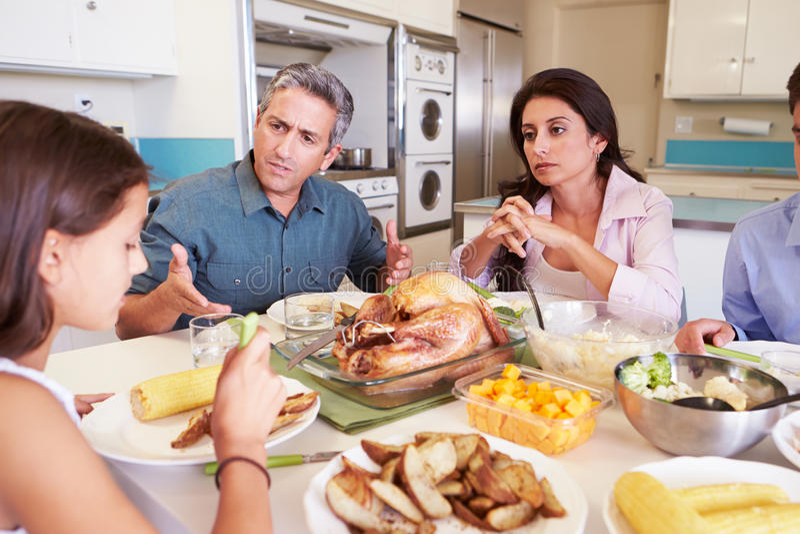 Familia que tiene discusión que se sienta alrededor de la tabla que come la comida fotografía de archivo
