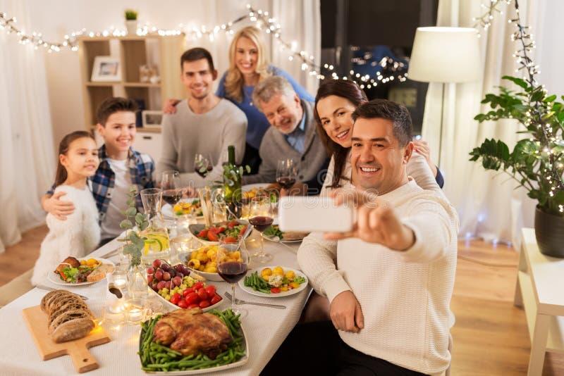 Familia que tiene partido de cena y que toma el selfie fotografía de archivo
