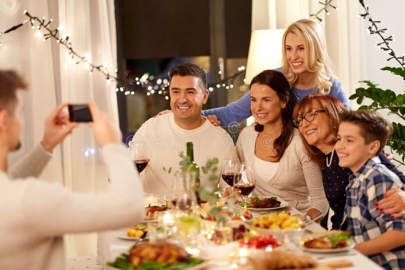 Familia que tiene partido de cena y que toma el selfie foto de archivo