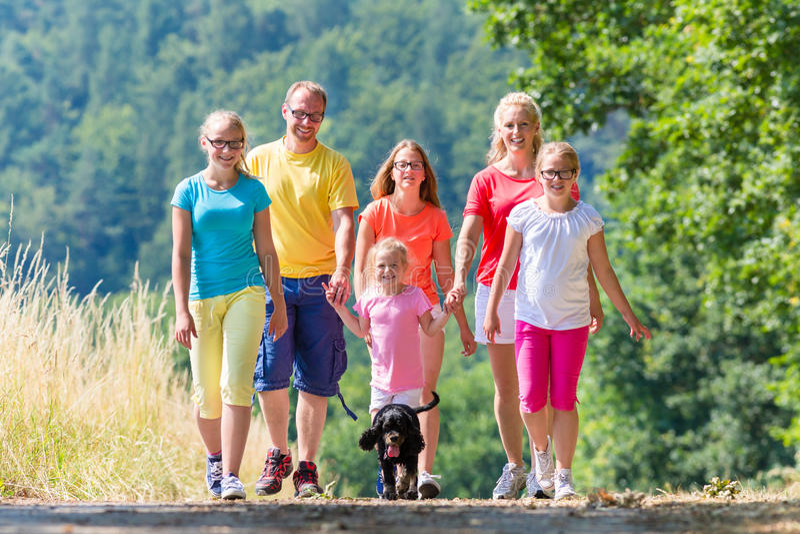 Familia que tiene paseo en la trayectoria en el bosque imagen de archivo libre de regalías