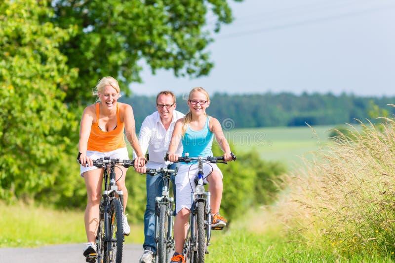 Familia que tiene viaje de la bicicleta del fin de semana al aire libre imagenes de archivo