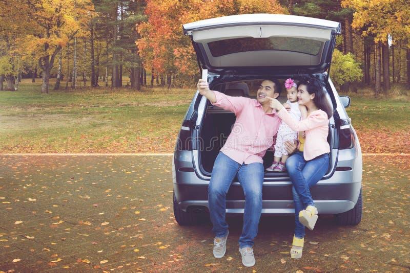 Familia que toma el selfie en coche en el parque del otoño imágenes de archivo libres de regalías
