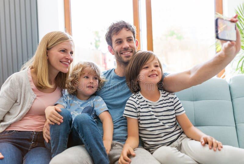 Familia que toma el selfie mientras que se sienta en el sof? en casa imagen de archivo libre de regalías