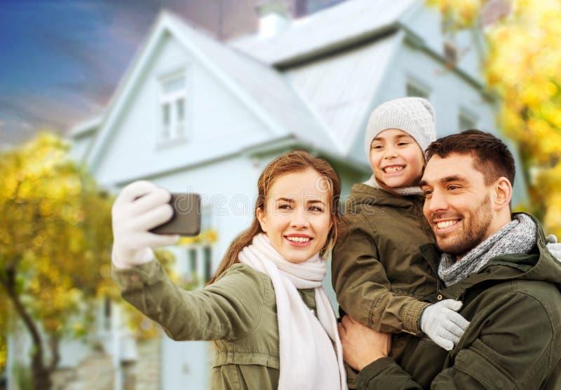 Familia que toma el selfie sobre casa en otoño foto de archivo