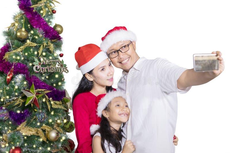 Familia que toma la imagen del selfie cerca del árbol de navidad imagenes de archivo