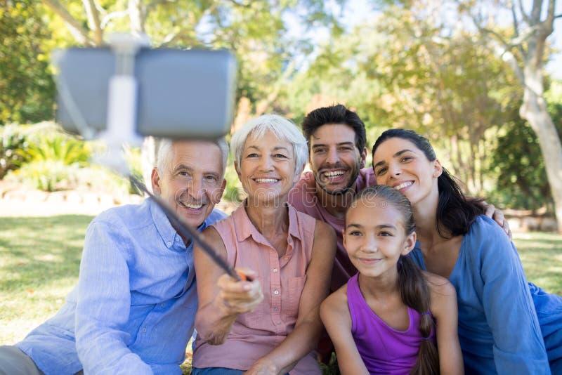Familia que toma un selfie en el parque imagen de archivo