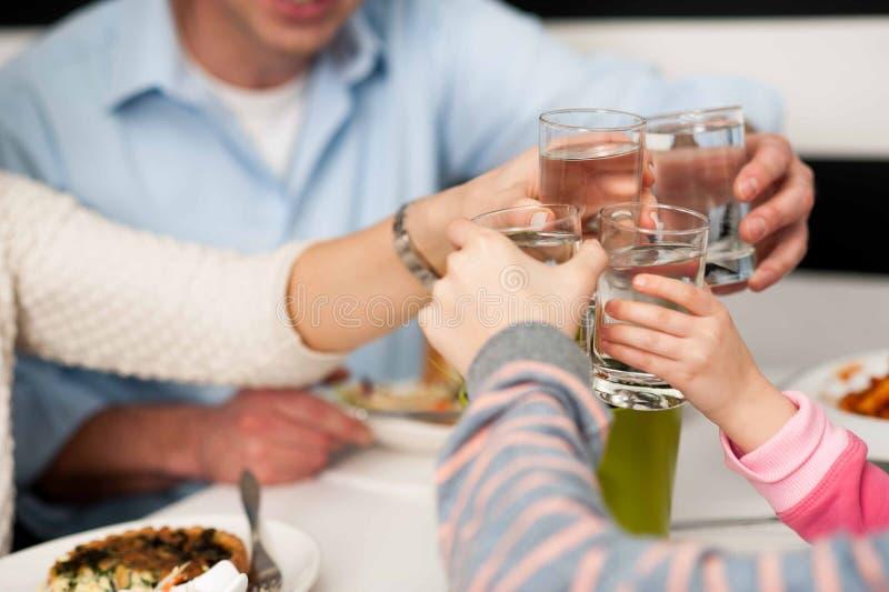 Familia que tuesta los vidrios de agua en la celebración imagenes de archivo