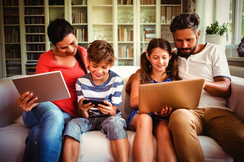 Familia que usa diversas tecnologías mientras que se sienta en el sofá imagen de archivo