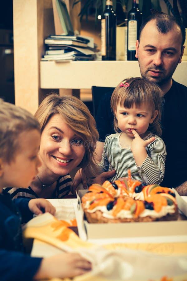 Familia que va a comer una torta imagen de archivo