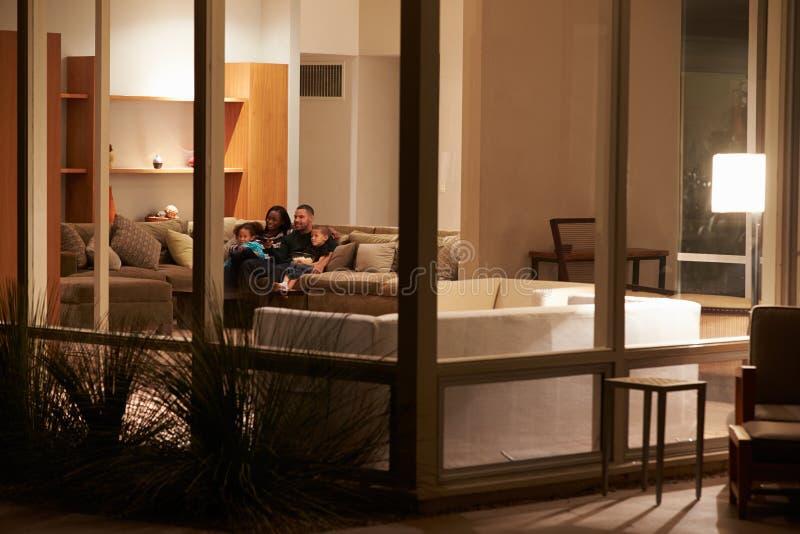 Familia que ve la TV en casa vista de exterior imagenes de archivo