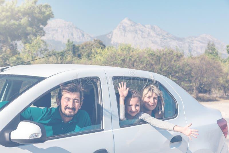 Familia que viaja junto en coche emocionado y feliz foto de archivo