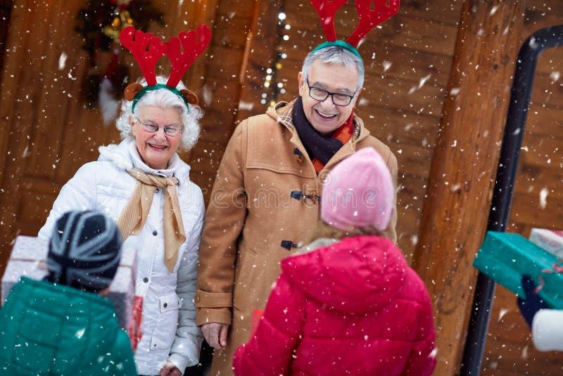 Familia que viene en casa celebrar la Navidad imágenes de archivo libres de regalías