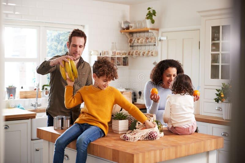 Familia Regresando A Casa De Un Viaje Comercial Usando Bolsas Libres De Plástico Desempaquetando Comestibles En Cocina fotos de archivo