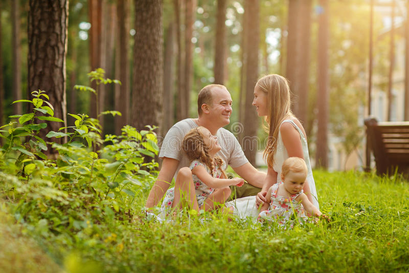 Familia - sentada rubia de la madre, del padre y de dos hijas en un su fotos de archivo