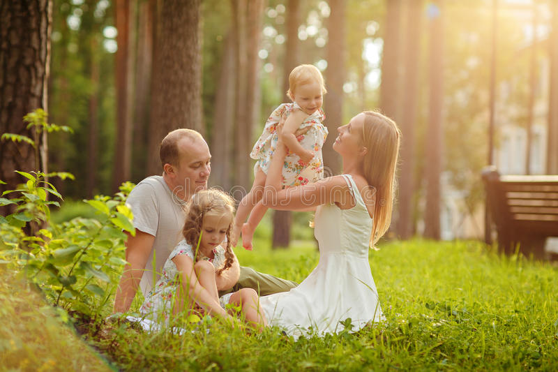 Familia - sentada rubia de la madre, del padre y de dos hijas en un su foto de archivo