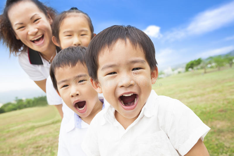 Familia sonriente asiática que juega el prado y día soleado imagenes de archivo