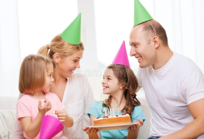 Familia sonriente con dos niños en sombreros con la torta foto de archivo libre de regalías
