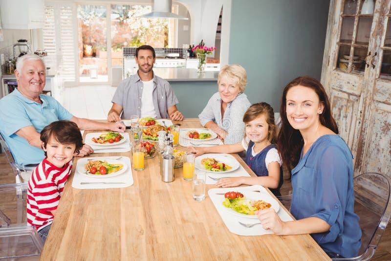 Familia sonriente con los abuelos que se sientan en la - El comedor de familia ...