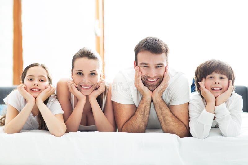 Familia sonriente en cama imagen de archivo libre de regalías