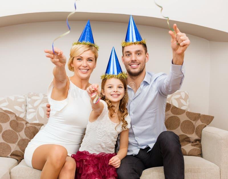Familia sonriente en sombreros azules con la torta foto de archivo libre de regalías