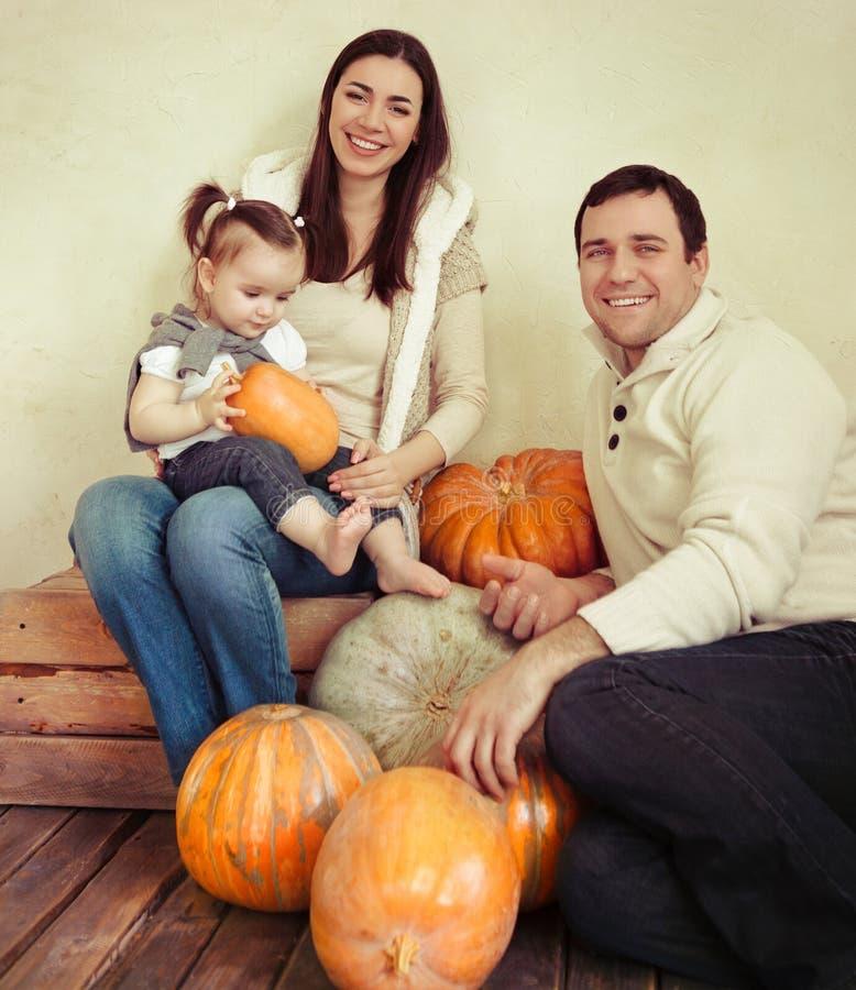 Familia sonriente feliz con el bebé de un año interior imagenes de archivo